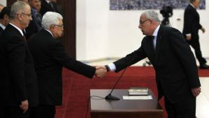 Palestinian Foreign Minister Riyad Al-Maliki (R) is sworn in along with the new Palestinian unity government in the presence of Palestinian president Mahmud Abbas (2nd-L) and Prime Minister Rami Hamdallah (L) in the West Bank city of Ramallah on June 2, 2014. (AFP PHOTO/ABBAS MOMANI)