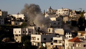 Smoke rises from the family home of Palestinian Ziad Awad in the town of Idna, 8 miles (13 kilometers) west of the West Bank city of Hebron, on Wednesday, July 2, 2014. (AP Photo/Nasser Shiyoukhi)