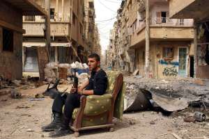 A member of the Free Syrian Army sits on a sofa in the middle of a debris-strewn street in Deir al-Zor, Syria, on April 2, 2013, Reuters