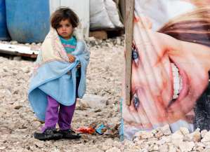 refugee girl covers herself with a blanket as she stands outside tents at a makeshift settlement in Bar Elias in the Bekaa valley