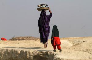 A woman carries laundry on her head, while heading home after washing in Charsadda, near Peshawar January 7, 2015. REUTERS/Fayaz Aziz