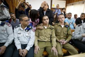 The father of an Israeli soldier who is charged with manslaughter, prays behind him in a military court during a remand hearing in Kiryat Malachi