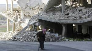 An elderly man walks past a damaged building in the rebel-controlled area of Maaret al-Numan town in Idlib province, Syria, December 21, 2015. REUTERS/Khalil Ashawi