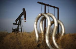 Pump jack and pipes are seen on an oil field near Bakersfield on a foggy day, California