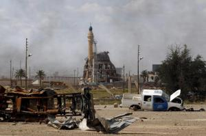 A damaged mosque is seen amidst destroyed vehicles and other debris in Tikrit, Iraq, April 1, 2015. The Iraqi government claimed victory over Islamic State insurgents in Tikrit on Wednesday after a month-long battle for the city supported by Shi'ite militiamen and U.S.-led air strikes, saying that only small pockets of resistance remained.