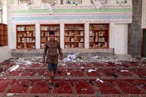 A Yemeni man inspects the damage following a bomb explosion at the Badr mosque in southern Sanaa on March 20, 2015.