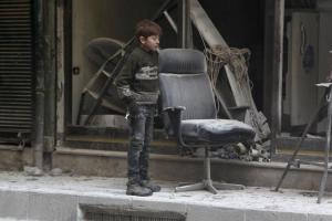 A boy inspects damage after airstrikes by pro-Syrian government forces in the rebel held Al-Shaar neighborhood of Aleppo, Syria February 4, 2016. REUTERS/Abdalrhman Ismail