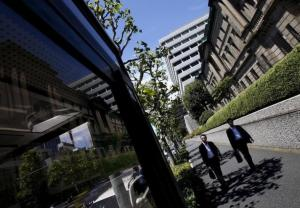 Pedestrians walk on a street in front of the Bank of Japan headquarters in Tokyo