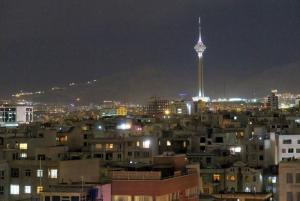 View shows Tehran's skyline at night with the Milad tower
