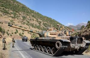Turkish soldiers in a tank and an armored vehicle patrol on the road to the town of Beytussebab in the southeastern Sirnak province, Turkey, September 28, 2015. REUTERS/Stringer