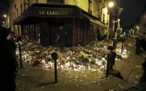 People pray outside Le Carillon restaurant, one of the attack sites in Paris, November 15, 2015. REUTERS/Jacky Naegelen