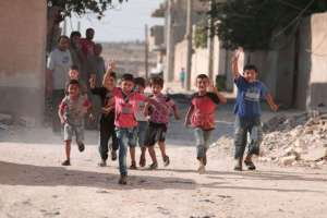 Children flash victory signs as they play in Manbij, in Aleppo Governorate.