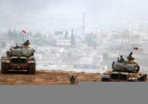 Turkish army tanks manoeuver as Turkish Kurds watch over the Syrian town of Kobani. (photo credit:REUTERS)