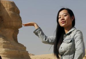 A Chinese tourist poses for a photo in front of the Sphinx at the Giza Pyramids on the outskirts of Cairo, Egypt March 2, 2016. REUTERS/Amr Abdallah Dalsh