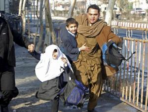 A man carries his son as they run after a blast near the Pakistani consulate in Jalalabad, Afghanistan