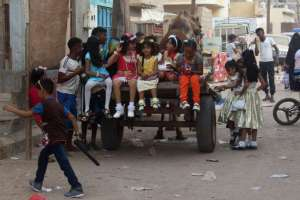 Yemeni girls sit on the back of a camel-drawn cart as people gather in the street during celebrations for Eid al-Fitr in Aden's northern Dar Saad district on July 6, 2016.PHOTO: AFP