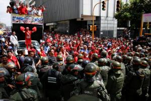 Supporters of Venezuela's President Nicolas Maduro shout slogans as they gather outside the National Assembly building during a session in Caracas