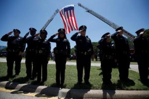 Police officers salute the hearse as they attend the funeral of slain Dallas police Sgt. Michael Smith in Dallas