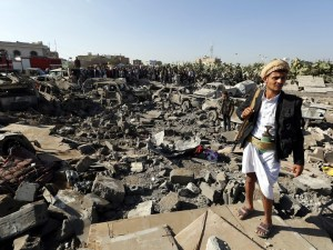 A member of the Houthi militia near vehicles destroyed by an airstrike in Sanaa, EPA