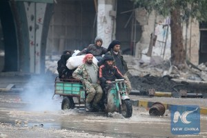 People ride a tricycle as they flee deeper into the remaining rebel-held areas of Aleppo, Syria December 7, 2016.