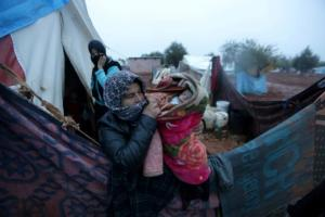 An internally displaced Syrian woman carries her child in the Bab Al-Salam refugee camp, near the Syrian-Turkish border