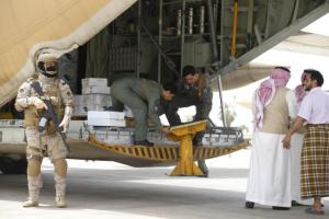 A Saudi soldier stands guard as servicemen on a Saudi military cargo plane prepare to unload aid at the international airport of Yemen's southern port city of Aden