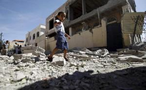 Boy walks past a house damaged by an airstrike in Yemen's capital Sanaa