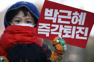 A South Korean child holds up a placard reading 'Park Geun Hye out' during a rally against the South Korean president on Dec 10, 2016.