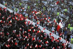 In this Friday, Sept. 30, 2011 file photo, Bahraini anti-government protesters wave flags and chant during a rally of thousands organized by Al-Wefaq.