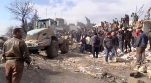A still image taken from a video obtained by Reuters shows people and a bulldozer moving debris after a fuel truck exploded in the centre of rebel-held Azaz, Syria