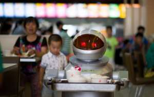 A robotic waiter carries food in a restaurant in Kunshan, China. (2014 photo by Johannes Eisele/Agence France-Presse via Getty Images)
