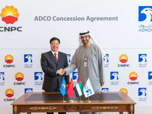 Sultan Ahmed Al Jaber shakes hands with Wang Yilin.