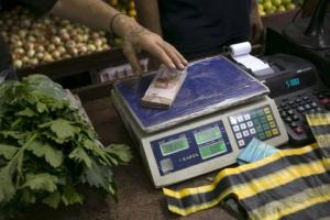 A clerk grabs a stack of Venezuelan 10 bolivars banknotes at a fruit and vegetable store in Caracas July 10, 2015. REUTERS/Marco Bello