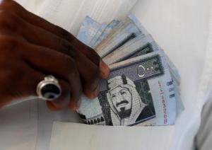 A Saudi man shows Saudi riyal banknotes at a money exchange shop in Riyadh