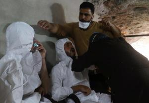 A man breathes through an oxygen mask as another one receives treatments, after what rescue workers described as a suspected gas attack in the town of Khan Sheikhoun in rebel-held Idlib