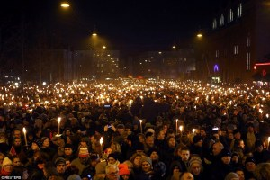 Hundreds of Danes hold candles and torches during a memorial service in Copenhagen for the two men who were killed in the double-attacks in the capital.