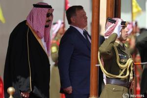 Jordan's King Abdullah II and Saudi Arabia's King Salman bin Abdulaziz Al Saud review honour guards at the airport in Amman