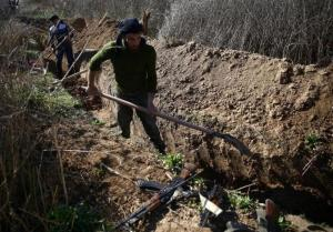 Fighters from the Free Syrian Army's Al Majd Brigades dig a trench in the rebel held besieged area of al-Marj in the Eastern Ghouta of Damascus