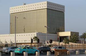 Cars drive past the building of Qatar Central Bank in Doha