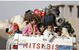 Children ride on the back of a pick-up truck as they flee Sana'a on April 6, 2015