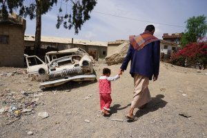 In the Harat Al-Masna'a slum in Sana'a, Yemen, a man walks with his three-year-old daughter which sits next to a former textile factory and hosts 231 families of former factory workers.
