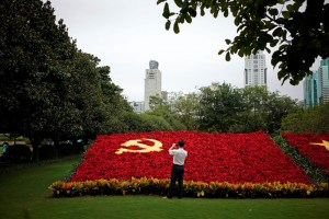 A man takes photos of a party flag of Communist Party of China made with flowers, which promotes the 19th National Congress of the Communist Party of China, in Shanghai