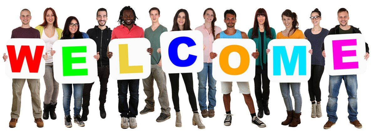 Smiling group of young multi ethnic people holding word welcome isolated on white