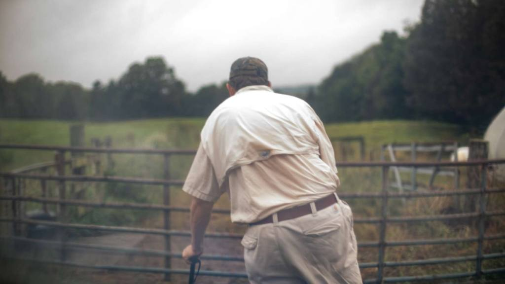 Photo of a man leaning on a cane in front of a gate to a cattle field.
