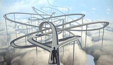 Business person standing at the start of a maze in the clouds