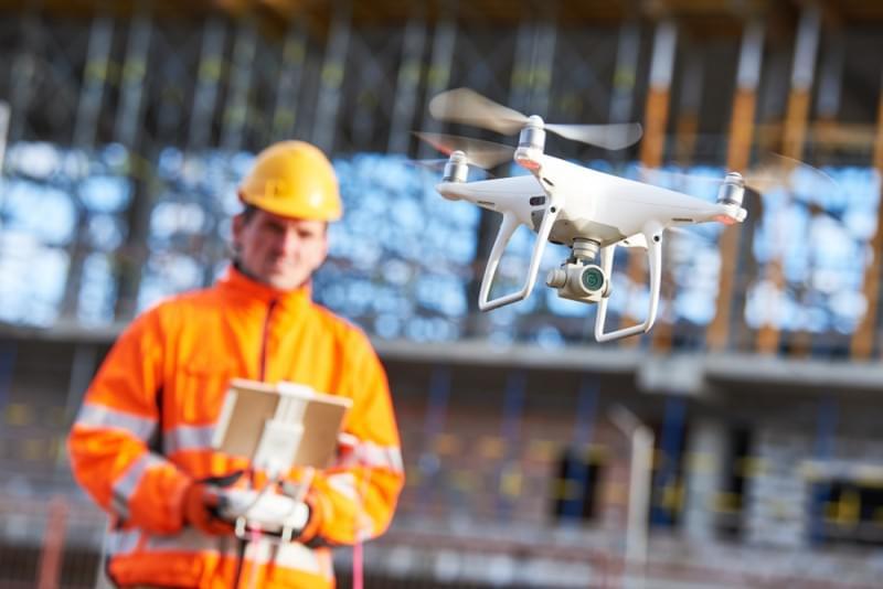 funcionário operando drones no canteiro de obras