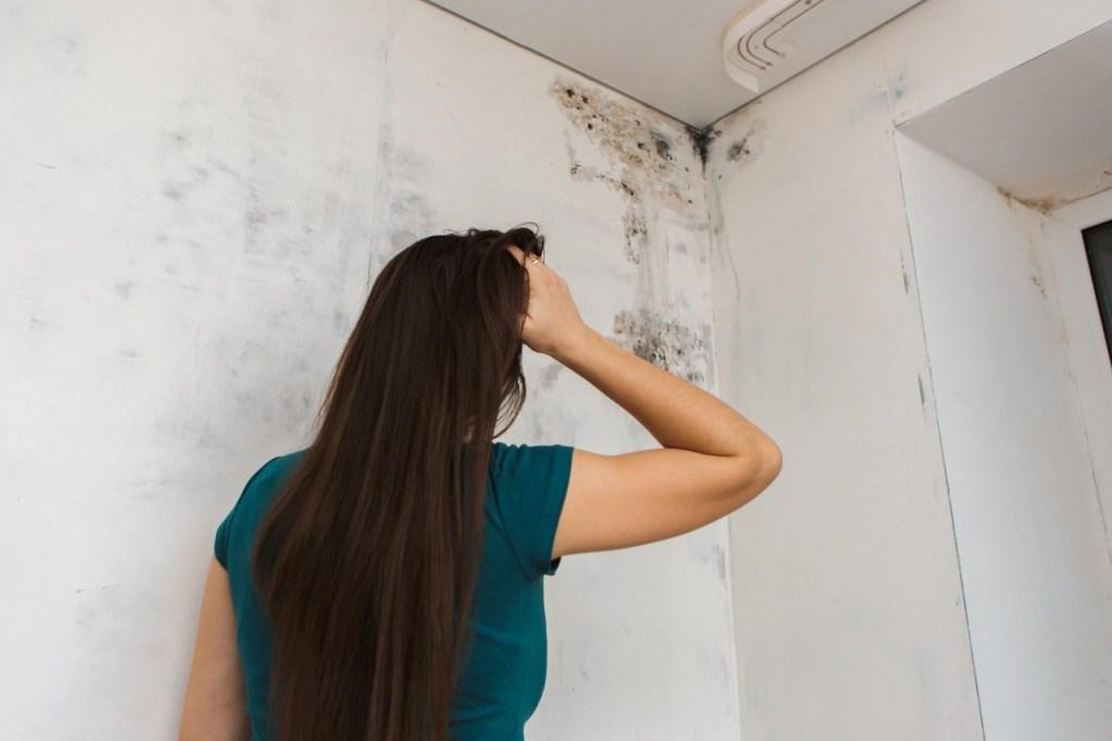 mulher olhando para mancha de umidade em parede