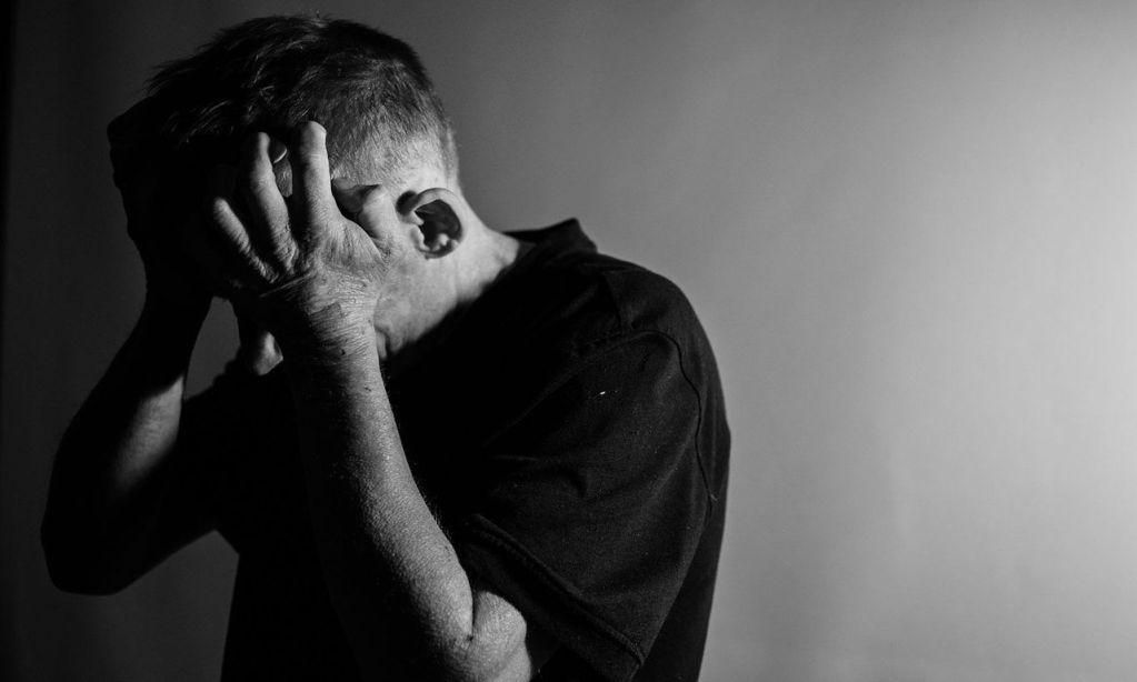 pessoa com depressão com as mãos na cabeça