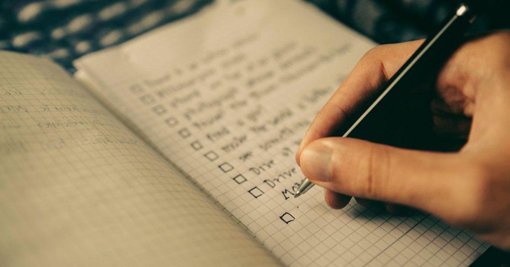 um caderno com anotações de lista de tarefas e uma mão marcando com caneta