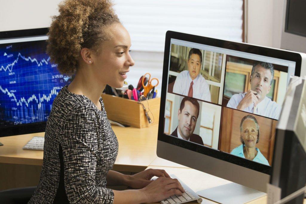 mulher em chamada de vídeo com outras pessoas num monitor